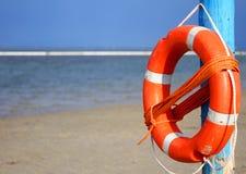 Pole with lifejacket at sea on the beach 2. Pole with orange lifejacket at sea on the beach 2 Stock Photography