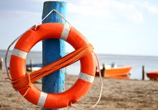 Pole with lifejacket at sea on the beach by the sea. Pole with orange lifejacket at sea on the beach by the sea Royalty Free Stock Photos