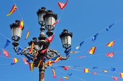 Pole with many flags. Against blue sky Stock Photos