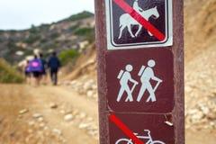 Pole mit dem Wandern des Zeichens und der Leute auf Hintergrund stockfotos