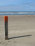 Pole with number 63 on the beach. Wooden pole with orange top and number 63 on the beach at Zandvoort, The Netherlands. Casting a shadow to the right side Stock Photo