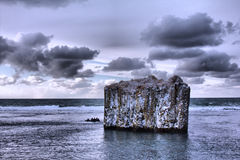 Pole in ocean. Rock with vertical walls. Basaltic parting, Royalty Free Stock Photography