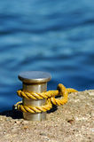 Pole and rope. A rope tied in the pole with blue water background Royalty Free Stock Image