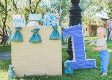 Pole trawa, postaci liczby jeden zabawki pobliski duży balon urodziny pierwszy rok życie chłopiec ono uśmiecha się na kamerze Obraz Stock