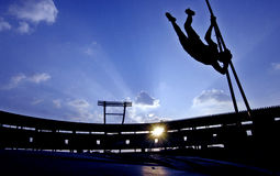 Pole Vault. An athlete attempt a pole vault while silhouetted by the sun against a cloudy sky Stock Photos