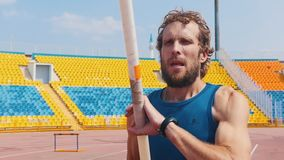 Pole vault - a bearded athletic man holding a pole and getting ready for the jumping - open stadium. Mid shot stock footage