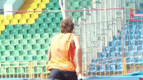 Pole vault - a man in orange shirt run up holding a pole in stadium. Mid shot stock video footage