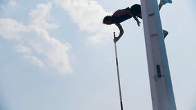 Pole vault training on the stadium outside- an athletic man jumping over the bar and falling down with the bar -. Unsuccessful attempt. Mid shot stock video