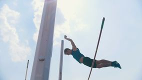 Pole vault training on the stadium outside- a man jumping over the bar and falling down with the bar - unsuccessful. Attempt. Mid shot stock video