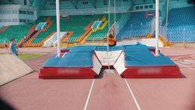 Pole vault - A young athletic woman jumps over the bar - stadium outdoors. Mid shot stock footage