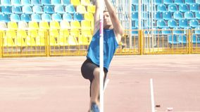 Pole vault - a young man running up and jumping over the bar - stadium. Mid shot stock video footage