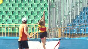 Pole vault - a young woman jumps over the bar in the stadium. Mid shot stock footage