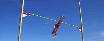 Pole vaulter. Panoramic view of a pole vaulter athlete just clearing the bar, and ready to release the pole. Beijing 2008 Olympic Games China Stock Photo