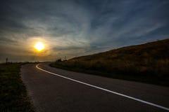 Pole złota trawa Opróżnia asfaltową drogę i zmrok - niebieskiego nieba duri Zdjęcie Royalty Free