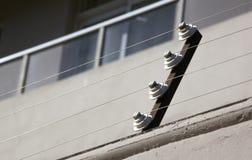 Poleas que apoyan la cerca eléctrica del edificio residencial Fotos de archivo
