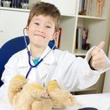 Polegar bonito de sorriso do doutor da criança pequena acima foto de stock royalty free