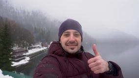 Polegar da exibição do homem acima no lago Ritsa na Abkhásia no inverno filme