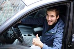 Polegar da exibição do homem novo acima, sentando-se na roda de um carro novo fotos de stock royalty free