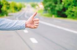Polegar da mão acima do fundo da estrada do carro da parada da tentativa do gesto Gesto do polegar ou de mão que viaja Certifique imagens de stock