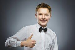 Polegar feliz bem sucedido da mostra do menino do retrato do close up acima do fundo cinzento fotos de stock royalty free