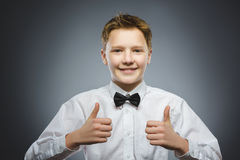 Polegar feliz bem sucedido da mostra do menino do retrato do close up acima do fundo cinzento fotografia de stock