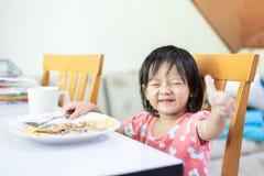 polegar pequeno da exibição da criança do bebê acima, comendo e para apreciar só o café da manhã imagem de stock royalty free