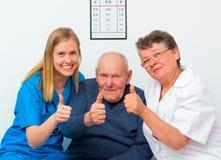 Polegares acima do homem idoso e dos seus cuidadors foto de stock royalty free