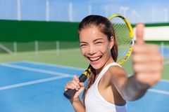 Polegares asiáticos felizes da menina do jogador de tênis acima do divertimento do jogo fotografia de stock