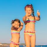 Polegares da mostra das crianças acima na praia foto de stock