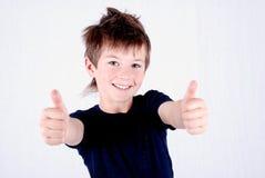 Polegares de sorriso da terra arrendada dois do menino considerável acima foto de stock