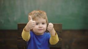 Polegares do aluno acima Instrução bem sucedida Retrato de um rapaz pequeno alegre que mostra os polegares acima do sinal usando  vídeos de arquivo