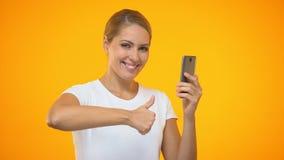 Polegares fêmeas felizes da exibição acima do smartphone da terra arrendada, compra em linha, Internet filme