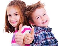 Polegares felizes do menino e da menina acima Foto de Stock Royalty Free