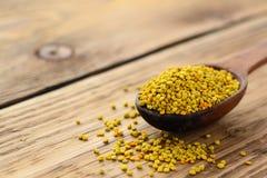 Polen de la abeja en cuchara sobre fondo de madera Ingrediente alimentario vegetariano de la dieta cruda orgánica sana - polen de Foto de archivo libre de regalías