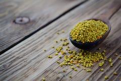 Polen de la abeja en cuchara sobre fondo de madera Ingrediente alimentario vegetariano de la dieta cruda orgánica sana - polen de Fotos de archivo