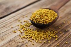 Polen de la abeja en cuchara sobre fondo de madera Ingrediente alimentario vegetariano de la dieta cruda orgánica sana - polen de Fotografía de archivo