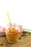Polen de la abeja en el tarro y la cuchara de cristal Foto de archivo libre de regalías