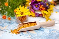 Polen en cucharada de madera con la flor amarilla en vidrio plástico Fotos de archivo