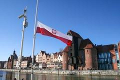 Polen-Flagge auf dem Hintergrund eines historischen Kranes in Gdansk, Polen lizenzfreie stockfotografie