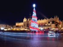 Polen, Krakau, HoofddieMarktvierkant en Doekzaal in de winter, tijdens Kerstmismarkten met Kerstboom worden verfraaid Stock Afbeeldingen