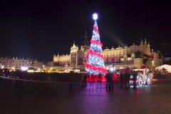 Polen, Krakow, huvudsaklig marknadsfyrkant och torkduk Hall i vinter, under julmässor som dekoreras med julgranen royaltyfria bilder