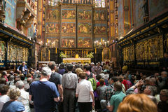 POLEN KRAKOW - MAJ 27, 2016: Turister i förväntan av öppningen av det huvudsakliga altaret av Stet Mary ' s-kyrka Arkivbild