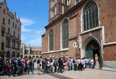 POLEN KRAKOW - MAJ 27, 2016: Turister som väntar i linje för att se öppningen av det huvudsakliga altaret i St Mary ' s-kyrk Royaltyfria Foton