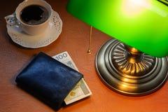 Polen pengar, Zloty, på ett stilfullt skrivbord som tänds med en packa ihop lampa royaltyfri bild