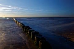 Polen som är baltisk över havssolnedgång Vågbrytare på den släta yttersidan av havet Royaltyfri Bild