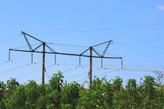 Polen und hängende Stromleitungen Stockfotos