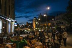 Polen - Warszawa - 09 05 2015 - Nattpanoramapeoplae som sitter av gatan som bygger den gamla staden Royaltyfri Fotografi