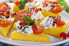 Polenta appetizers with ricotta and bacon. Polenta appetizers with herbed ricotta and bacon Stock Photo