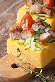Polenta avec le lard, légumes sur la verticale de conseil en bois photographie stock libre de droits