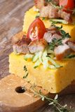 Polenta with bacon, vegetables on wooden board vertical Royalty Free Stock Photography